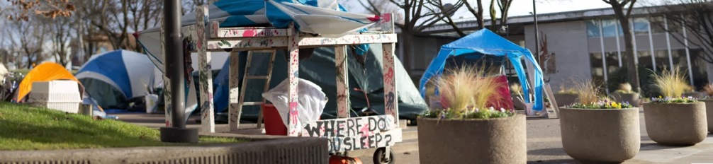 Homelessness is a hot political issue in Eugene. Here, members of a makeshift community occupy the plaza in front of city hall, Eugene City Center. A display in front of the camp asks passersby a poignant question - where do you sleep?